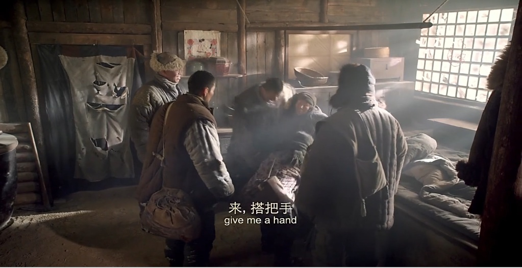 Figure 8. PLA soldiers helping an ill elder villager onto her bed (kang)